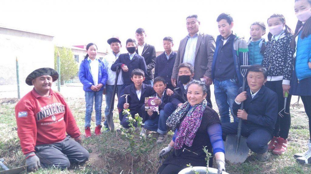 Mongolische Schüler pflanzen Aroniasträucher